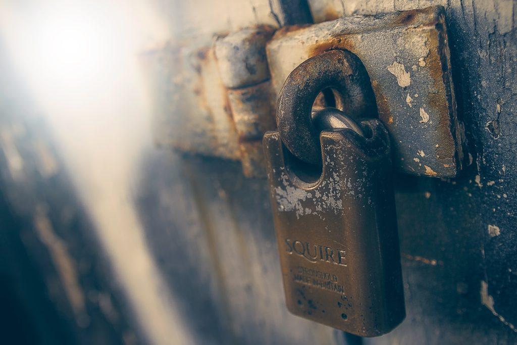 rostige Tür, die mit einem Schloss gesichert ist