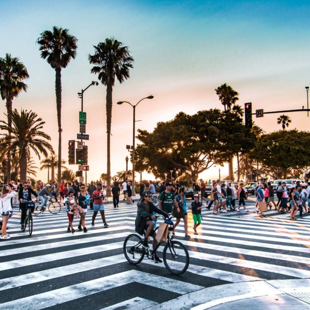 Viele Menschen laufen über einen Zebrastreifen