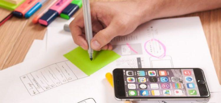 Schreibtisch mit Zettel, Stiften und einem Handy